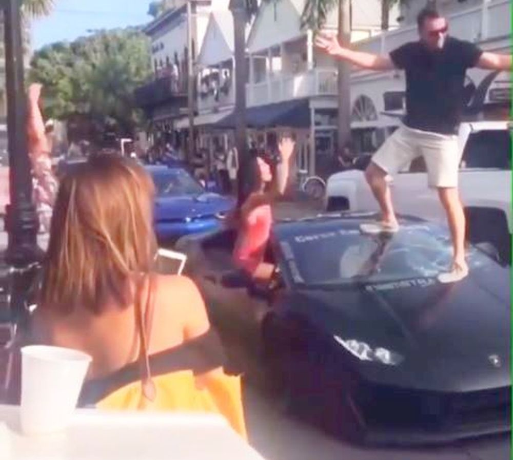 Guy stand on Lamborghini windshield